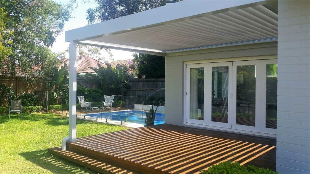 Opening roof in backyard with timber deck and pool